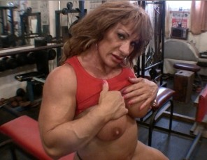 Female bodybuilder Wild Kat does bench presses in the gym, building the mature muscles of her pecs, biceps and abs. It gets her so wet, she just has to masturbate her wet pussy and big clit. You get to watch her pumped-up pussy in close-up. Wait for my leg workout, she says. That's gonna be hot.